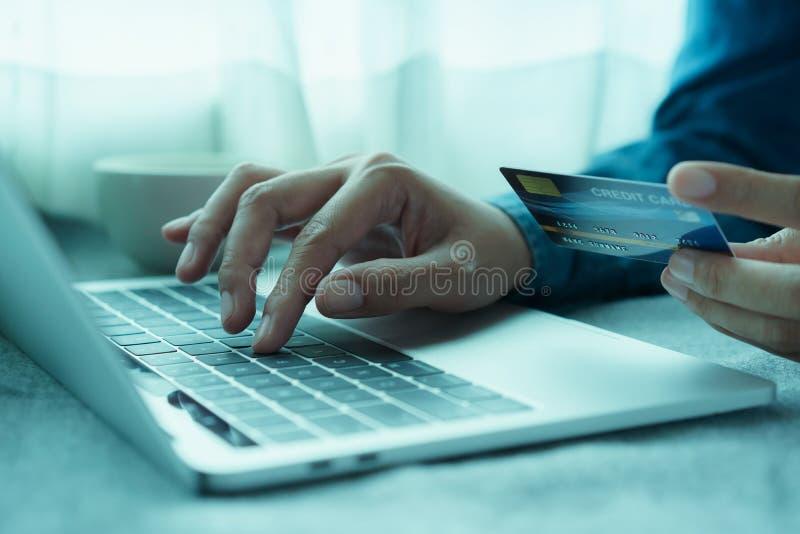 Den nära övre handen av affärsmän köper direktanslutet med en kreditkort Män använder bärbara datorn och gör online-transaktioner royaltyfria foton