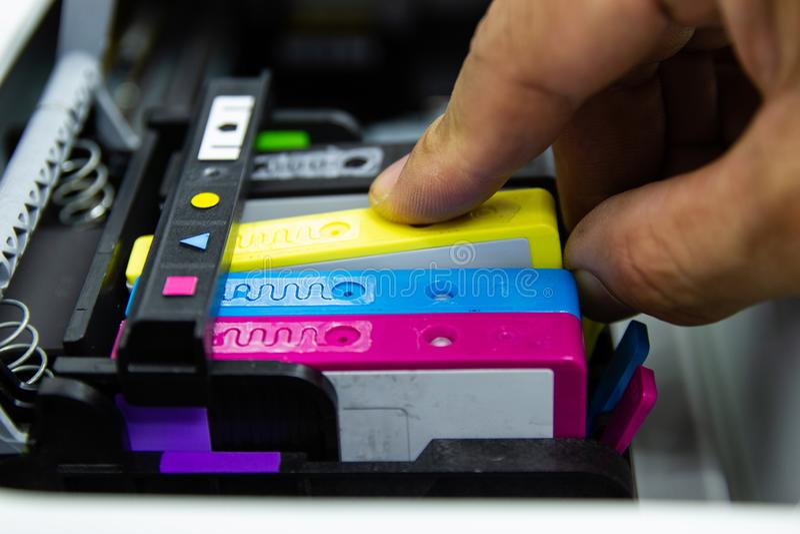 Den nära övre handmannen satte kassetten för bläckstrålar för färgskrivaren royaltyfria foton