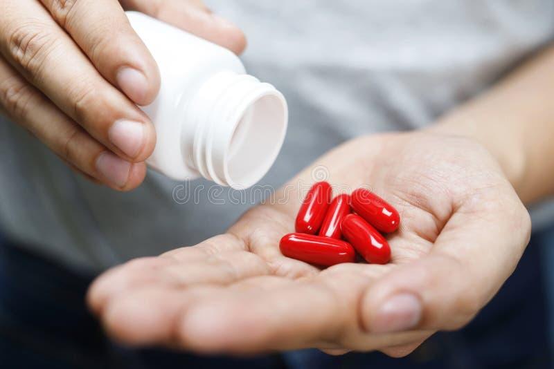 Den nära övre manhanden som rymmer en medicin, med häller pillervitaminet arkivbilder