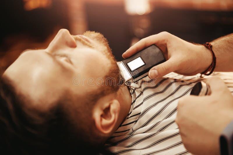 Den nära övre mannen rakas i frisersalong med rakapparaten Händer av hjälpmedlet för frisörraminnehav royaltyfri foto