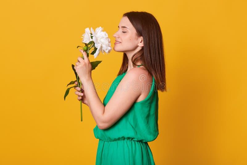 Den nära övre profilståenden av damen som bär gröna sundress, håller härliga blommor i händer på gul studiobakgrund och att vara  royaltyfria bilder