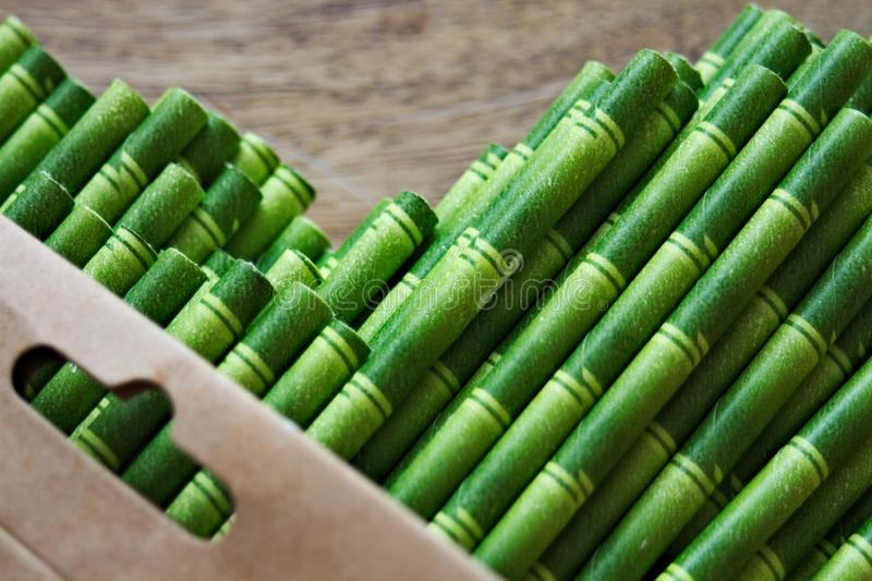 Den nära övre sikten av pappers- sugrör för bambu som kommer ut ur en kartong, lägenhet lägger royaltyfri bild
