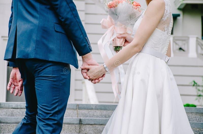 Den nära övre sikten av den unga bruden och brudgummen som rymmer händer, sceen utomhus- royaltyfri fotografi