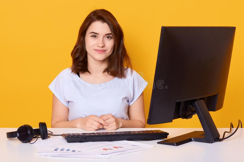 Den nära övre ståenden av den härliga unga brunettkvinnlign som framme sitter på det vita skrivbordet av datoren hemma, har onlin arkivbild