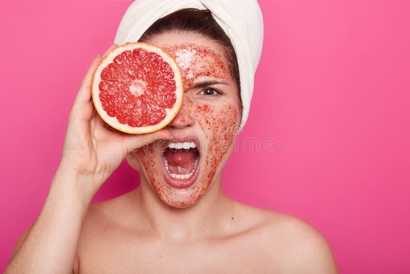 Den nära övre ståenden av den unga kvinnan med ilsket ansiktsuttryck, skrin i badrum med den vita handduken på huvudet, täck fotografering för bildbyråer