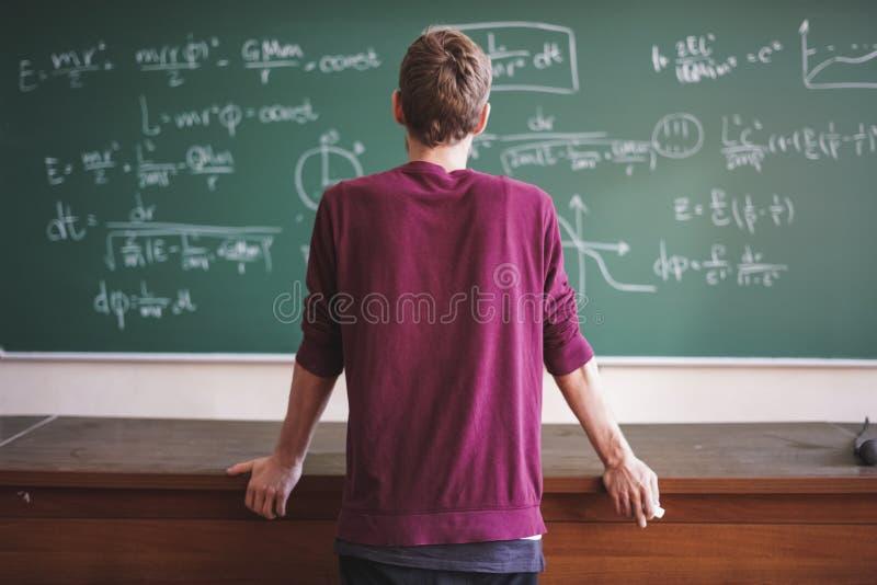 Den nära ståenden av barn uppsökte professorläraren i tillfälligt med svart tavla med formler bakom arkivfoton