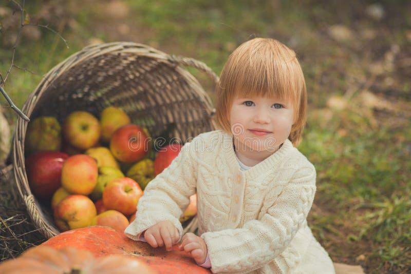 Den nära ståenden behandla som ett barn flickan med bärande elfenbenfärg för blont rött hår som den vita tröjan tycker om byn för arkivfoton