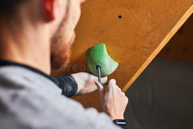 Den nära tillbaka sikten av bouldereren med skruvande håll för det fysiska handikappet på vaggar upp väggen fotografering för bildbyråer