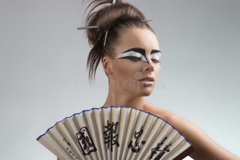 Den nätt brunetten i japan utformar looks på lämnat arkivfoton