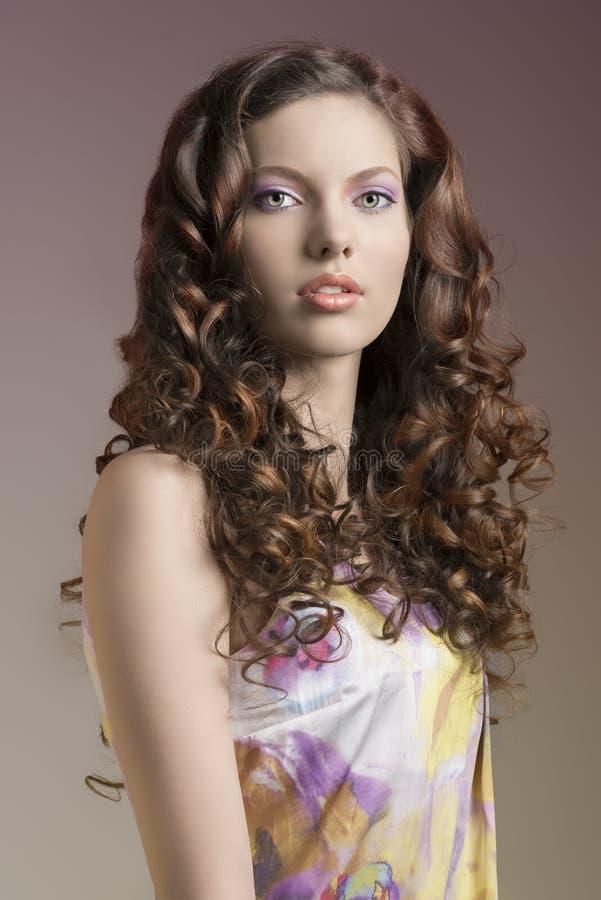 Den nätt brunetten med lockigt hår och gräsplan synar royaltyfri bild