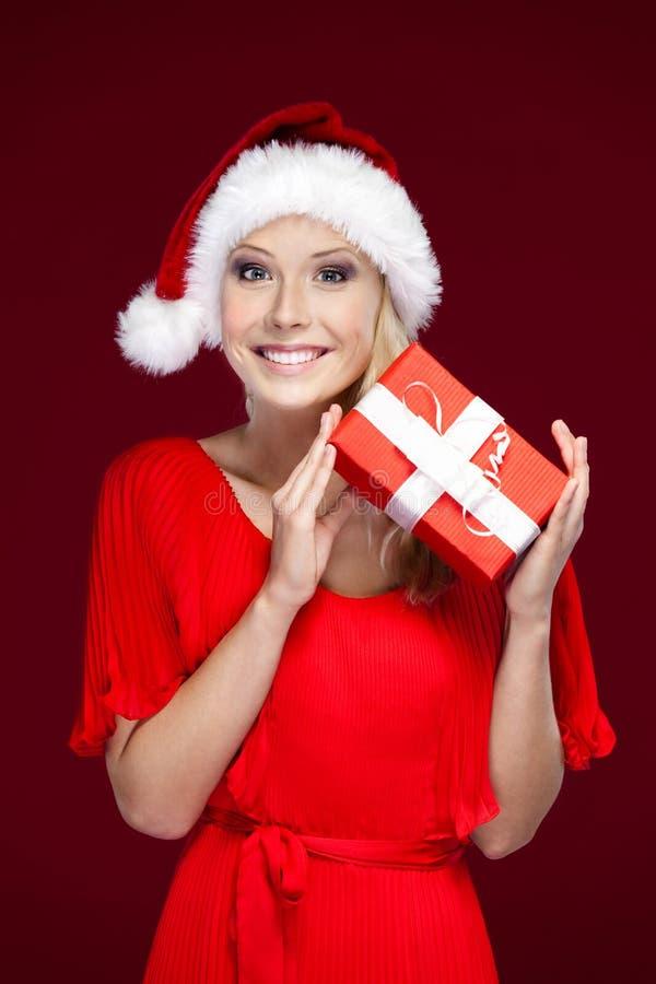 Den nätt kvinnan i jul cap händer en present royaltyfri foto