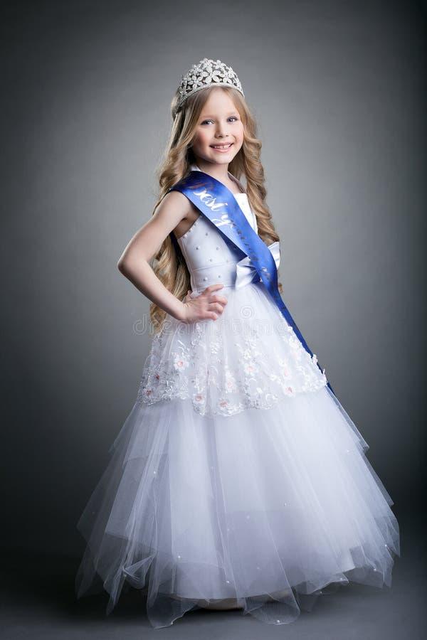 Den nätt liten flicka i tiara och lång vit klär arkivfoton