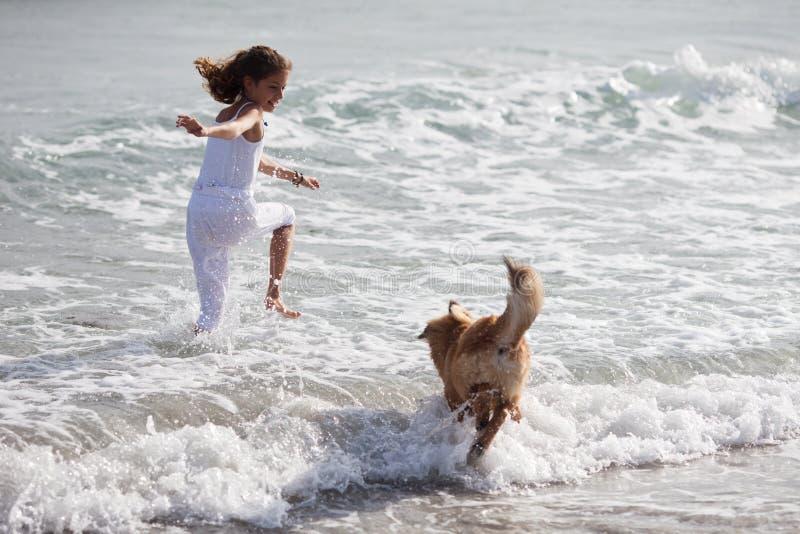 Den nätt ung flicka kör med en hund i havsvattnet arkivbilder