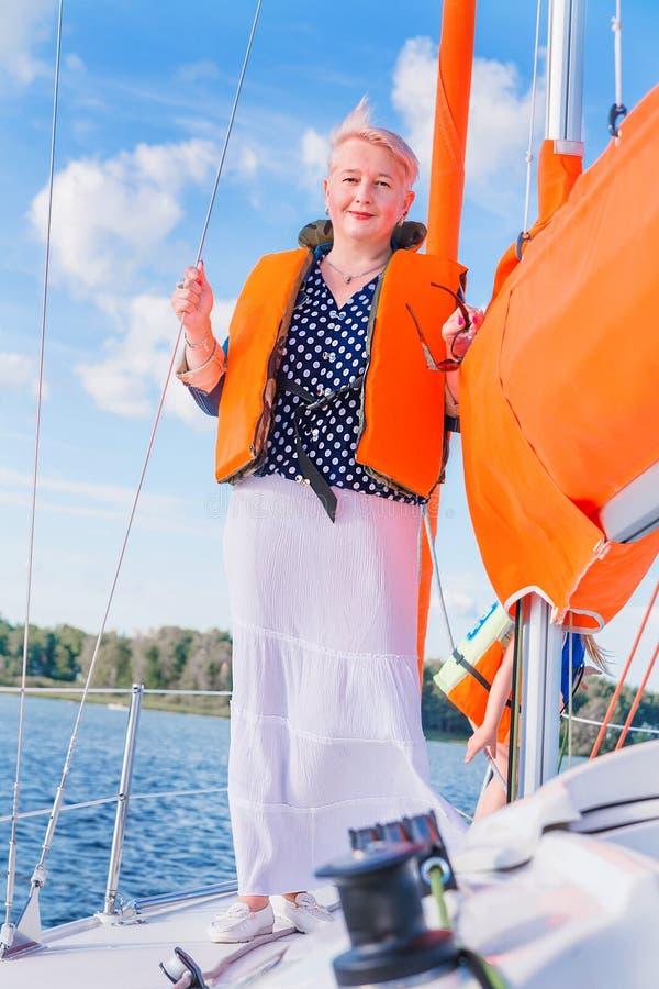 Den nätta äldre kvinnan tycker om att segla Vertikalt foto arkivfoton