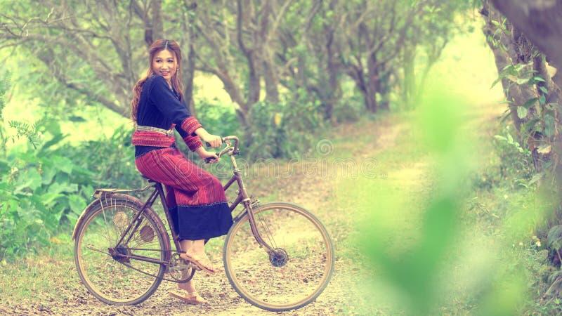 Den nätta asiatiska flickan sitter på cykeln parkerar in royaltyfria bilder