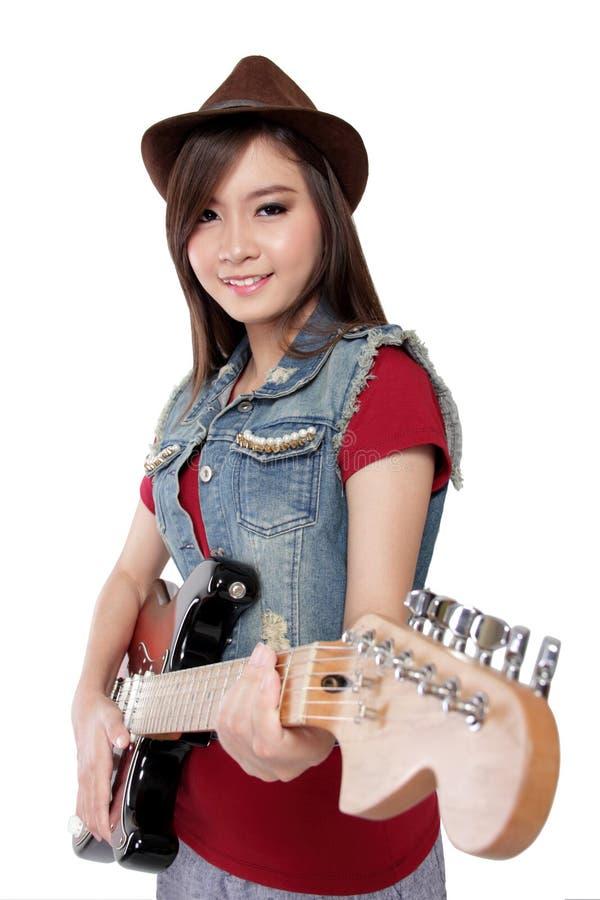 Den nätta asiatiska gitarristflickan ler på kameran, på vit backgroun royaltyfria foton