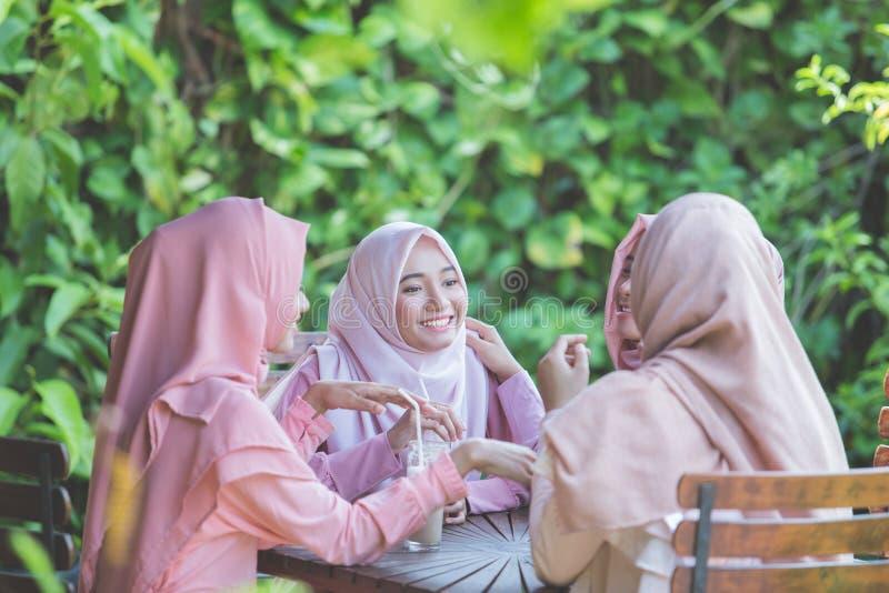 Den nätta asiatiska muslimkvinnan som har gyckel i kafé samman med, frien royaltyfria foton
