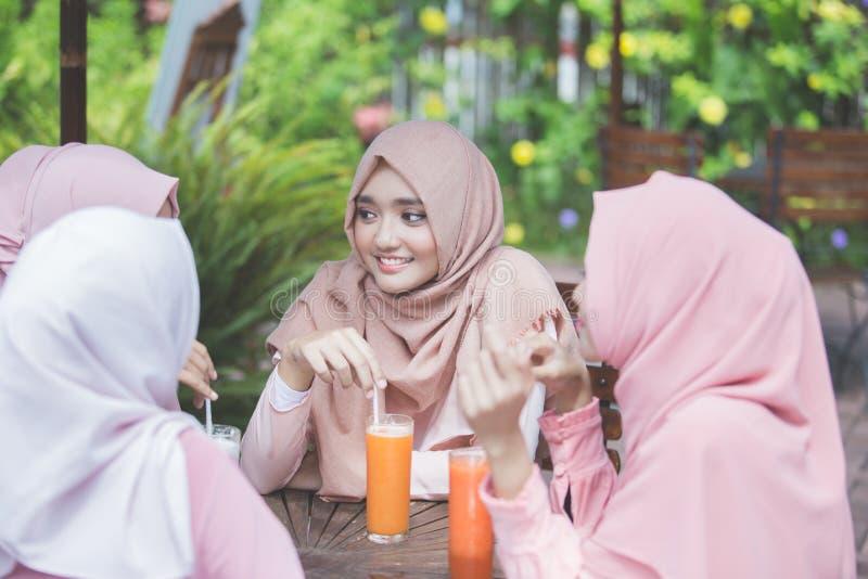 Den nätta asiatiska muslimkvinnan som har gyckel i kafé samman med, frien arkivbild