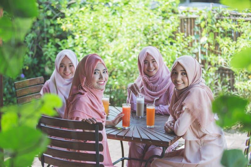 Den nätta asiatiska muslimkvinnan som har gyckel i kafé samman med, frien royaltyfria bilder