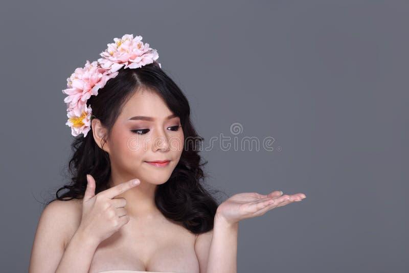 Den nätta asiatiska unga kvinnan med blommatiaran, närvarande tomt gömma i handflatan royaltyfria bilder