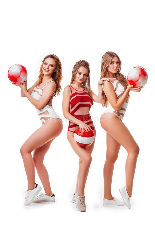 Den nätta bikinin modellerar hållande röda bollar i studio arkivbilder