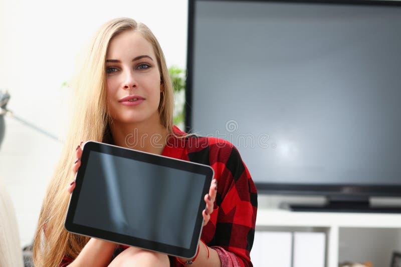 Den nätta blonda hållbärbara datorn för den unga kvinnan i armar sitter på soffan arkivfoto