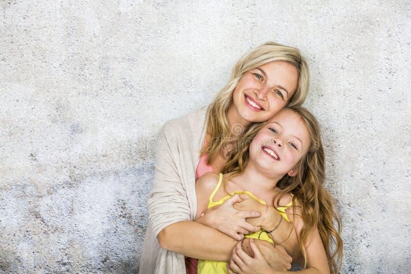 Den nätta blonda unga modern poserar och kelar med hennes dotter framme av en betongvägg och att ha mycket gyckel arkivbild