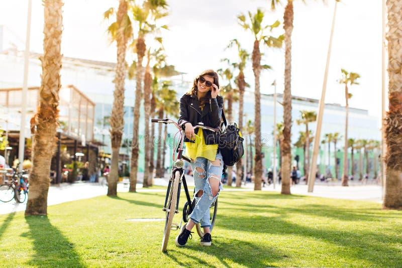 Den nätta brunettflickan med en cykel på gräs omger gömma i handflatan Hon kyler i solljus som ler till kameran royaltyfria bilder