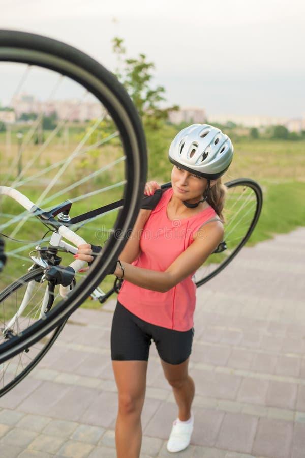 Den nätta Caucasian idrottskvinnan utarbetar med cykeln utanför arkivfoton