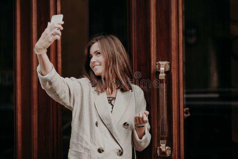 Den nätta förtjusande kvinnan gör selfie med den smarta telefonen, iklädd regnrock, poserar utomhus-, använder modern teknologi,  royaltyfri bild