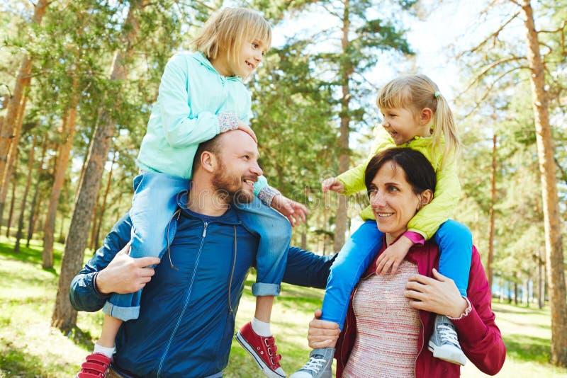 Den nätta familjen som tycker om vårdag parkerar in arkivfoto