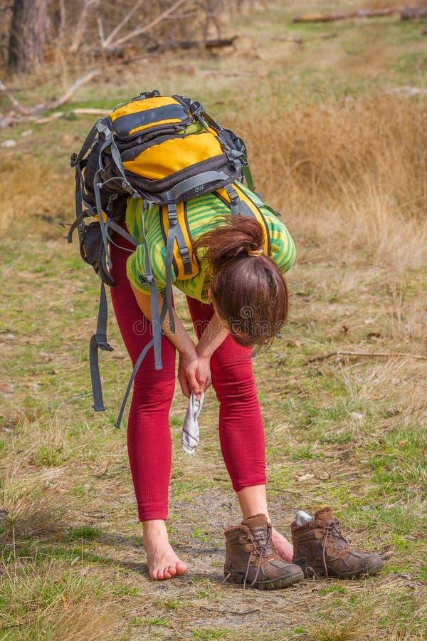 Den nätta flickabenägenheten utan skor i den vita kvinnan för skogen har en vila, når den har trekking länge royaltyfria foton