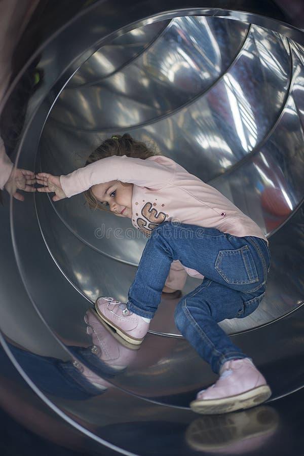 Den nätta flickan förvanskar på en glidbana i lekplatsen arkivfoto