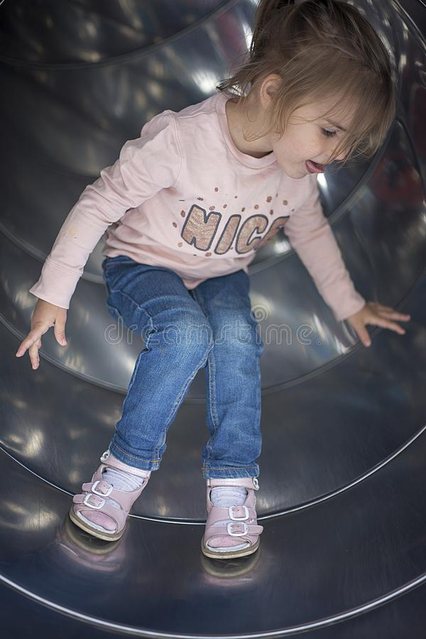 Den nätta flickan har gyckel på en glidbana i lekplatsen arkivfoton