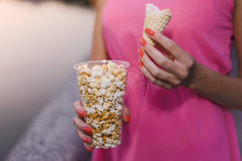 Den nätta flickan i rosa klänning rymmer popcorn och glass i aftonen på solnedgången royaltyfri fotografi