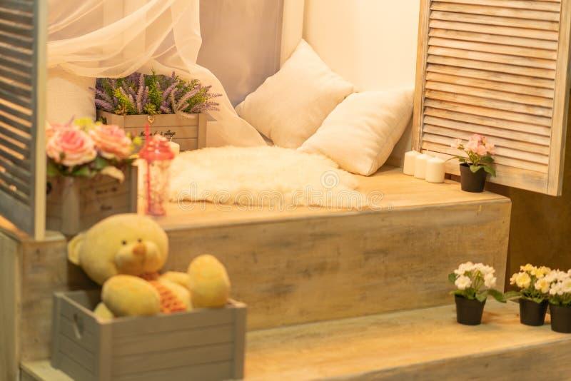 Den nätta flickan i rosa paljetter klär att ha vilar på aftonfönsterfönsterbräda med ljusa kulor, kuddar, blommor och leksaker arkivbilder