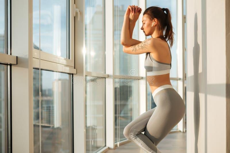 Den nätta flickan i sportig överkant och damasker som öva yoga, poserar lyssnande musik över stort fönster royaltyfri foto