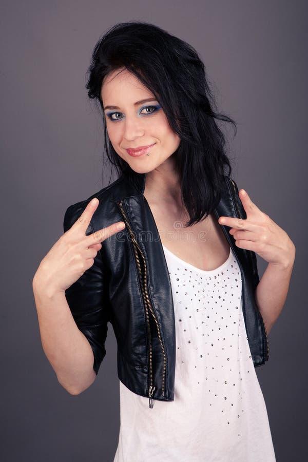 Den nätta flickan i visning för läderomslag gör en gest med henne händer royaltyfri fotografi