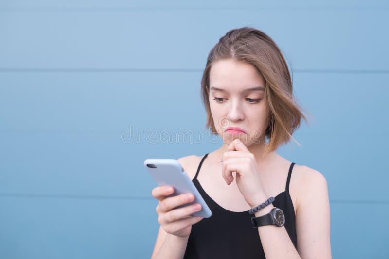 Den nätta flickan med en ledsen framsida ser en smartphone på bakgrunden av en blå pastellfärgad vägg fotografering för bildbyråer