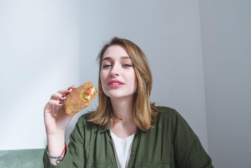 den nätta flickan med en smörgås i hennes händer ser kameran och leendena Kvinnan har frukostsnabbmat arkivbild