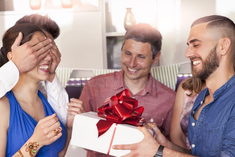 Den nätta flickan med födelsedagkakan som mottar gåvan från hans, frien royaltyfri fotografi