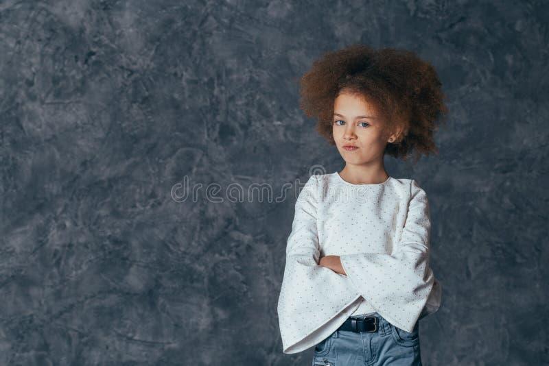 Den nätta flickan med lockigt hår ser bort och tänker fotografering för bildbyråer