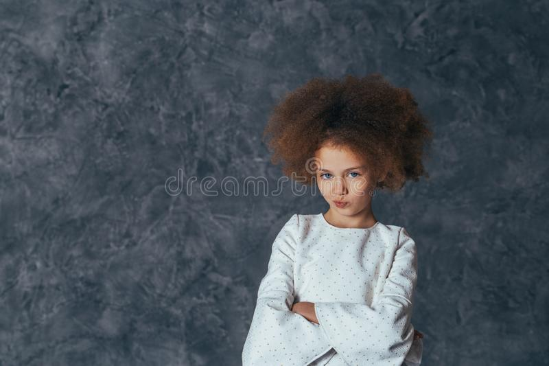 Den nätta flickan med lockigt hår ser bort och tänker royaltyfria bilder