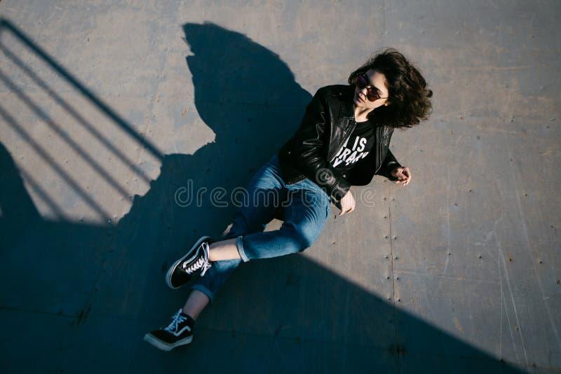 Den nätta flickan med lockigt hår som vilar i skateboard, parkerar Ståenden av den härliga unga flickan i skridskon parkerar Ung  royaltyfria bilder