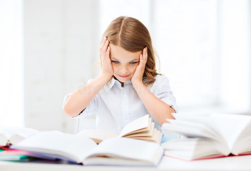 Den nätta flickan med många bokar på skolan royaltyfri bild