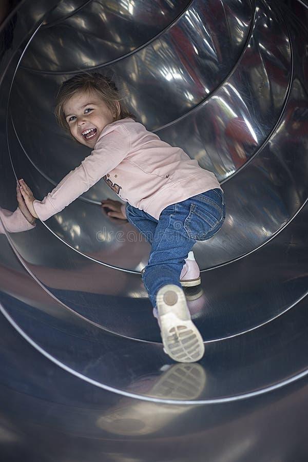 Den nätta flickan rullar på en glidbana i lekplatsen royaltyfri bild