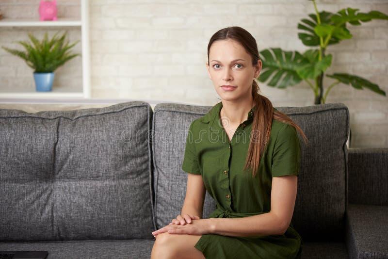 den nätta flickan sitter på en soffa royaltyfri fotografi