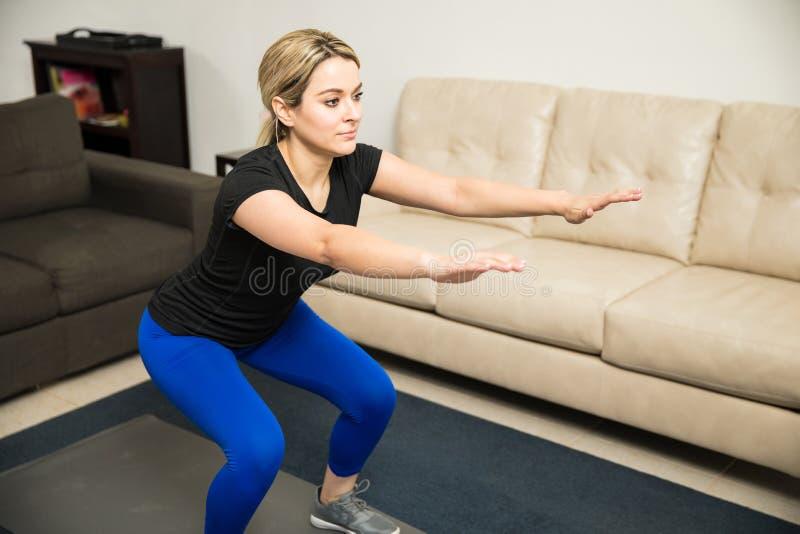 Den nätta flickan som gör något, squats hemma royaltyfria bilder