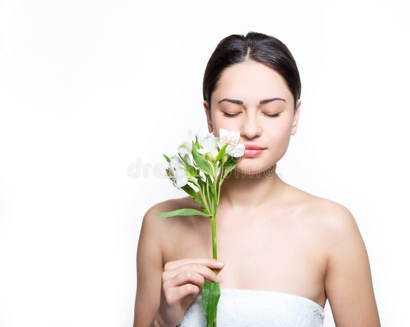 Den nätta flickan som rymmer en blomma nära framsidan och, inhalerar dess fragr royaltyfria foton