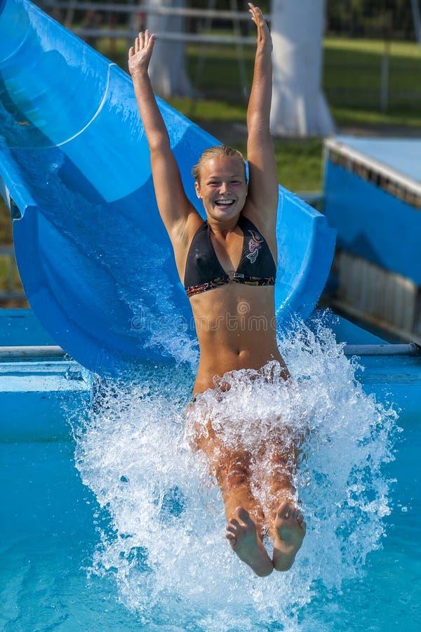 Den nätta flickan tycker om vatten-parkera i sommar royaltyfria foton